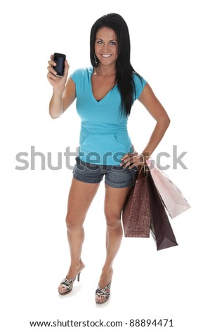 Full length photo of attractive young woman standing on white background holding smart phone and shopping bags.