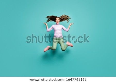 Full length photo of beautiful crazy lady jump high throwing long curly hairdo air rejoicing wear purple jumper green pants footwear isolated blue teal pastel color background
