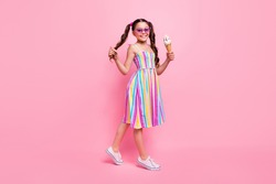 Full length photo of beautiful little lady two cute wavy tails good mood hold big gelato walk street wear colored dress summer sneakers sun specs isolated pastel pink color background