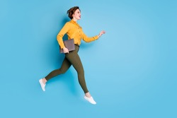 Full length photo of beautiful pretty business lady jump high hold notebook rushing conference wear yellow shirt green pants shoes isolated bright blue color background