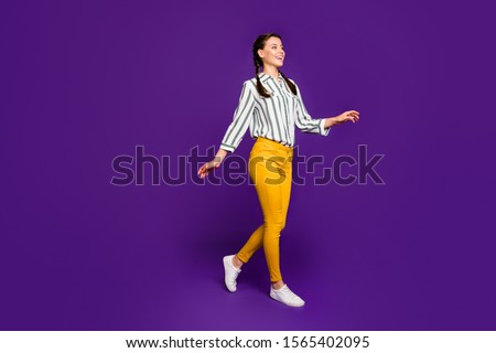 Full length photo of beautiful pretty lady toothy beaming smiling going down street good sunny day weather wear striped shirt yellow trousers isolated purple color background