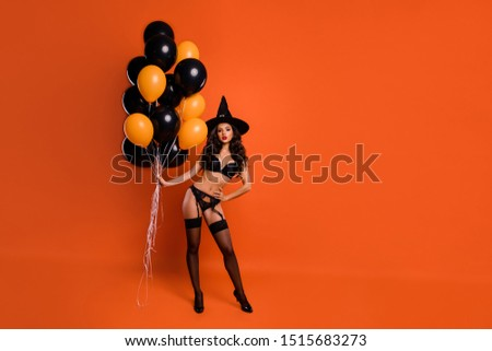 Full length photo of beautiful red lips nude lady hold air balloons demonstrate perfect shapes naughty mood wear bikini tights witch cap isolated orange background
