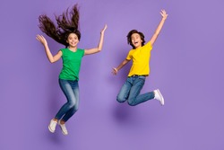 Full length photo of brother and sister jump up fly hair wear t-shirt jeans isolated on violet color background