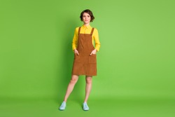 Full length photo of charming confident girl wear yellow shirt short overall footwear isolated green color background