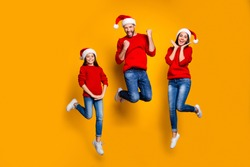 Full length photo of cheeerful funky funny excited jump positive charming family with people rejoicing with beginning of vacation together isolated over vivid yellow background wear red sweater jeans