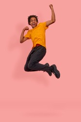 Full length photo of cheerful African American man jump raise fists to scream yes celebrate a victory or rejoicing with sales starting, wear orange casual t-shirt isolated over pink background