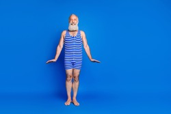 Full length photo of cheerful elderly man wear bathing suit striped copyspace summer swim isolated on blue color background