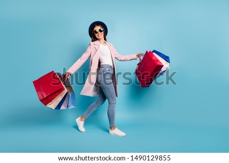 Full length photo of cheerful funky lady tourist in eyewear eyeglasses go shopping buy sales discount wear pink retro vintage coat denim jeans isolated over blue background
