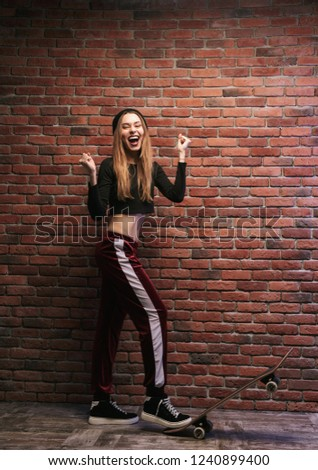 Full length photo of cheerful sporty girl standing against brick wall with skateboard #1240899400