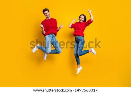 Full length photo of cheerful woman and man jump raise fists scream yes celebrate victory wear red sweater denim jeans isolated over yellow background