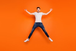 Full length photo of crazy funky guy jump high up spread hands legs good mood open mouth wear striped t-shirt jeans sneakers isolated bright orange color background