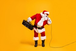 Full length photo of crazy grey white hair santa claus with beard hold boom box sing pop star song on christmas x-mas disco wear headwear cap isolated bright shine color background