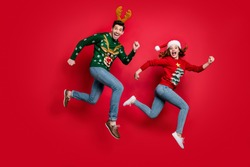 Full length photo of crazy jumping couple excited by x-mas discounts prices wear ugly ornament jumpers isolated red color background