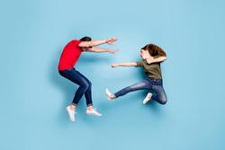 Full length photo of crazy mad two people spouses woman disagree jump fight kick man fall wear green red t-shirt denim jeans sneakers isolated over blue color background