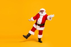 Full length photo of crazy santa claus with grey beard listen jolly holly music headset dance x-mas christmas party wear sunglass cap isolated bright shine color background