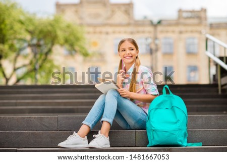 Full length photo of cute child with pigtails ponytails sit near university wearing checkered plaid t-shirt denim jeans  having rucksack backpack