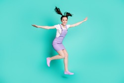 Full length photo of cute young girl jump raise hands play game wear purple short overall sneakers isolated teal color background