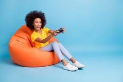Full length photo of dark skin brunette girl play game joystick sit bean bag wear yellow t-shirt isolated on blue color background