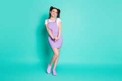 Full length photo of dreamy pretty girl hold hands look empty space wear violet short overall footwear isolated teal color background