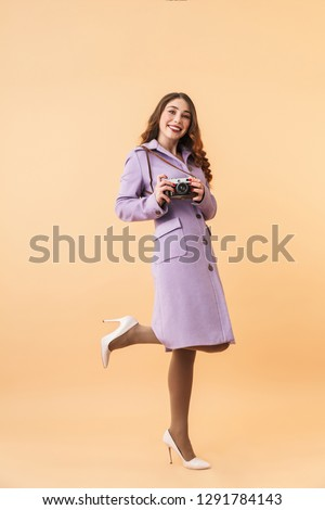 Full length photo of elegant woman 20s with long hair smiling and holding retro camera standing isolated over beige background