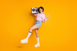 Full length photo of energetic positive youth girl hold listen boom box cassette music make v-sign enjoy discotheque wear pink jumper denim isolated over bright shine color background