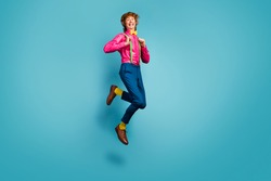 Full length photo of enthusiastic cheerful guy jump enjoy spring free time holiday jump pull suspenders wear trendy pink shoes isolated over blue color background