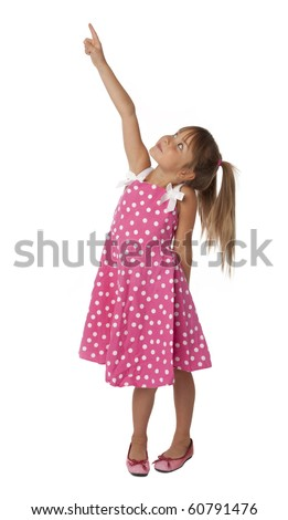 Full length photo of five year old girl in polka dot dress pointing upward. Isolated on white background.
