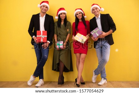 Full-length photo of four smartly dressed people, two females and two males, wearing red New Year hats and posing with nicely wrapped gifts of different size and color. #1577054629