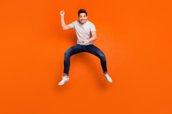 Full length photo of funky guy jump high up pretending horse riding rushing speed fast excited mood wear striped t-shirt jeans sneakers isolated bright orange color background