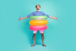 Full length photo of funny aged seaman swimmer stand inside three colorful circle lifebuoy wear striped sailor shirt white shorts flip-flops isolated teal color background