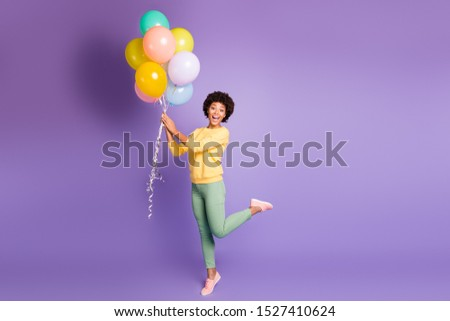 Full length photo of funny funky girl hold many baloons get gift on her birthday feel astonished expression scream wow omg wear casual style clothing isolated violet purple color background