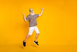 Full length photo of funny funky lucky old bearded man in green eyewear eyeglasses raise fists scream yeah celebrate victory jump wearing leopard shirt shorts isolated over yellow background