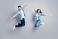Full length photo of funny lady handsome guy crazy two people jumping high up spread hands like wings flying away wear casual denim shirts outfit isolated grey color background