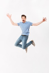 Full-length photo of funny man 30s in casual t-shirt and jeans jumping with arms throwing up isolated over white background