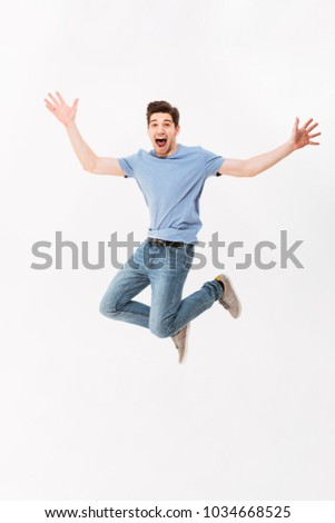 Full-length photo of funny man 30s in casual t-shirt and jeans jumping with arms throwing up isolated over white background #1034668525