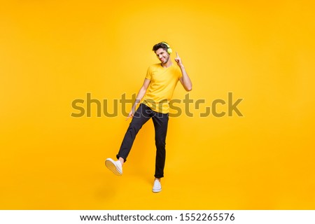 Full length photo of handsome guy at students party listening youth music earflaps dancing youngster moves wear casual t-shirt pants isolated yellow color background