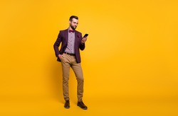 Full length photo of handsome rich clothes stylish guy well-dressed business man browsing telephone read news wear plaid shirt blazer trousers shoes isolated yellow color background