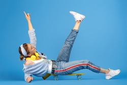 Full length photo of happy carefree young woman with yellow headphones sitting on penny or skateboard over blue background.