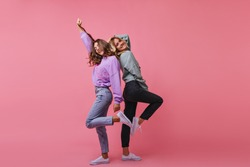 Full-length photo of inspired girls funny dancing together. Indoor shot of cheerful best friends standing on bright background.