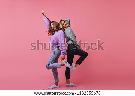 Full-length photo of inspired girls funny dancing together. Indoor shot of cheerful best friends standing on bright background. #1182355678