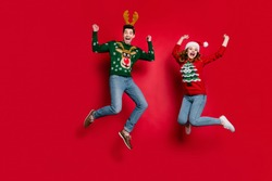 Full length photo of lady and guy jumping excited by x-mas discounts wear ugly ornament jumpers and headwear isolated red color background