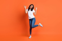 Full length photo of lady dance open mouth wear white t-shirt jeans sneakers isolated orange color background