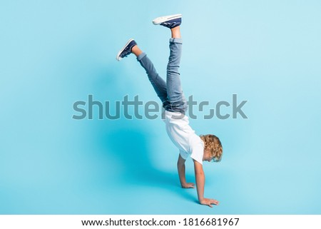 Full length photo of little kid stand hands raise legs wear white shirt jeans sneakers isolated blue color background Stockfoto ©