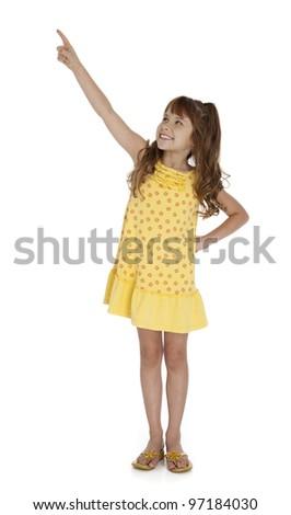 Full length photo of little wearing yellow summer dress pointing upward, on white background. - stock photo