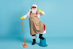 Full length photo of pensioner old man grey beard hold mop leg bucket raise thumb-up wear santa x-mas costume apron rubber glove suspender sunglass cap isolated blue color background