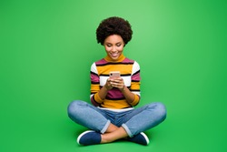 Full length photo of positive afro american girl blogger sit legs crossed folded use cellphone post comment share repost wear bright shine outfit isolated over green color background
