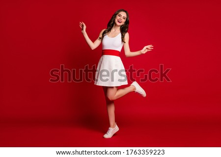 Full length photo of pretty cute lady good mood toothy beaming smiling flirty raise one leg walk down street summer time wear white short dress shoes isolated red color background