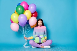 Full length photo of pretty girl sit floor legs crossed hold balloons gift box wear pullover isolated blue color background