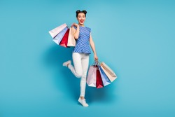 Full length photo of pretty lady carry many packs spree addicted shopaholic rejoicing shopping center wear dotted blouse white pants footwear isolated blue color background
