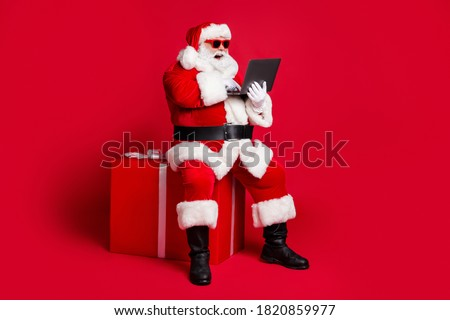 Full length photo of retired old man white beard sit giftbox hold laptop take orders online wear x-mas santa costume glove coat belt sunglass cap boot isolated red color background